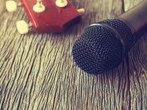 Schwarzes Mikrofon auf hölzerner Platte mit Gitarre herein aus Fokusba heraus Lizenzfreies Stockbild