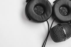 Schwarzes Mikrofon und schwarze Kopfhörer auf einem weißen Hintergrund Stillleben des Karaokes oder des Tonstudios Lizenzfreie Stockfotos