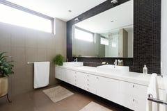 Schwarzes Mosaik deckte splashback und doppeltes Beckenbadezimmer mit Ziegeln Stockbilder