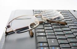 Schwarzes netbook mit Gläsern Stockfotos