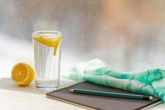 Schwarzes Notizbuch des Designers, Glas Mineralwasser mit Zitrone, Fensterhintergrund lizenzfreie stockbilder