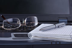 Schwarzes Notizbuch mit dem Notizblockfeder- und -glaslügen lizenzfreie stockfotos