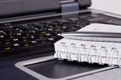Schwarzes Notizbuch mit Notizblock und Feder lizenzfreie stockfotografie