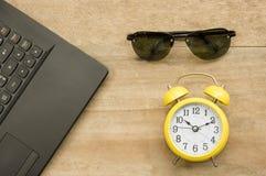 Schwarzes Notizbuch und gelbe Uhr mit Augenglas auf hölzernem stockbild