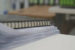Schwarzes Notizbuch und Stapel des weißen Dokuments lizenzfreies stockbild