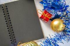 Schwarzes Papiernotizbuch mit Leerseiten- und Weihnachtssaisondekorfotohintergrund Lizenzfreie Stockfotos