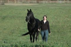 Schwarzes Pferd und Frau Stockfotografie