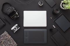 Schwarzes, photographer& x27; s-Schreibtisch mit Weinlesekamera, -laptop und -tablette Schwarzer Hintergrund Flache Lage lizenzfreies stockbild