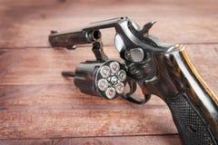 Schwarzes Revolvergewehr mit Kugeln auf hölzernem Hintergrund Stockbilder