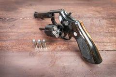 Schwarzes Revolvergewehr mit Kugeln auf hölzernem Hintergrund Stockfoto