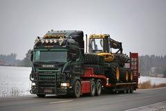Schwarzes Scania V8 transportiert halb Ponsse Forest Machinery Lizenzfreies Stockfoto