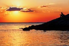 Schwarzes Schattenbild des jungen Mannes sitzend auf Sonnenuntergangseestrand stockfotografie