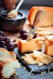 Schwarzes Schieferbrett mit dem verschiedenen Käse, verziert mit Trauben, Brot und Honig Lizenzfreies Stockfoto