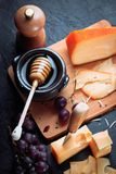 Schwarzes Schieferbrett mit dem verschiedenen Käse, verziert mit Trauben, Brot und Honig Lizenzfreie Stockbilder