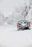 Schwarzes schneebedecktes Auto, das auf Winterstraße steht Lizenzfreies Stockfoto