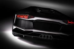 Schwarzes schnelles Sportauto im Scheinwerfer, schwarzer Hintergrund Glänzend, neu, luxuriös lizenzfreie abbildung
