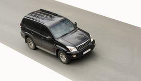 Schwarzes sehr großes suv Auto treibt schnell an Stockfotografie