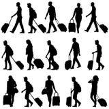 Schwarzes silhouettiert Reisende mit Koffern an Stockbild