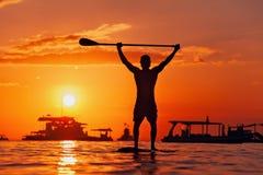 Schwarzes Sonnenuntergangschattenbild des Paddelinternatsschülers stehend auf SUP lizenzfreie stockfotos