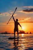 Schwarzes Sonnenuntergangschattenbild des Paddelinternatsschülers stehend auf SUP lizenzfreie stockfotografie