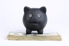 Schwarzes Sparschwein, das auf Stapel des Geldamerikaners hundert Dollarscheine auf weißem Hintergrund steht Stockfotos