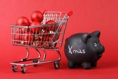 Schwarzes Sparschwein mit weißem Text Weihnachten und vollem Einkaufskorb von roten matten und glatten Weihnachtsbällen auf rotem Stockbild