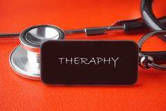 Schwarzes Stethoskop auf rotem Hintergrund lizenzfreie stockfotos