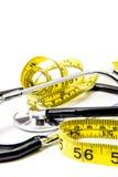 Schwarzes Stethoskop u. gelbes Diätband auf Weiß stockfotos