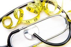 Schwarzes Stethoskop u. gelbes Diätband auf Weiß lizenzfreies stockbild