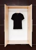Schwarzes T-Shirt auf hölzernen Aufhängern in einem Wandschrank Stockfotos