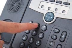 Schwarzes Telefon des Büros mit der Hand Lizenzfreies Stockfoto