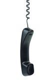 Schwarzes Telefon mit der Hand festgemachtes Hängen am Netzkabel Stockbilder