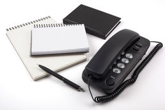 Schwarzes Telefon und Notizbücher auf weißem Hintergrund Stockfotos