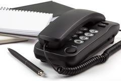 Schwarzes Telefon und Notizbücher auf weißem Hintergrund Lizenzfreie Stockfotografie