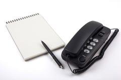 Schwarzes Telefon und Notizbuch auf weißem Hintergrund Lizenzfreie Stockfotografie