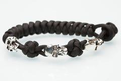 Schwarzes umsponnenes Armband mit den Schädeln auf Weiß Lizenzfreies Stockfoto