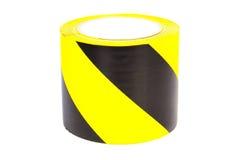 Schwarzes und gelbes warnendes Band auf weißem Hintergrund Stockfoto