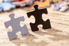 Schwarzes und Grey Jigsaw Puzzle Pieces auf Tabelle Lizenzfreie Stockfotos
