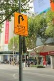 Schwarzes und orange Zeichen der Wende nur an der Ecke von Straßen Bourke und Swanston in Melbourne CBD Lizenzfreie Stockfotografie
