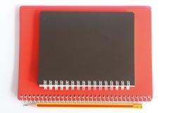 Schwarzes und rotes Notizbuch Stockfotografie