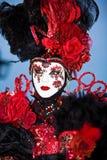 Schwarzes venetianisches Kostüm mit roten Rosen Lizenzfreies Stockfoto
