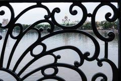 Schwarzes warf aufwändiges Gitter des Stadtdammzauns von Jekaterinburg mit Ansicht des Tempels auf Blut durch es lizenzfreie stockfotos