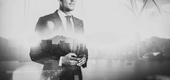 Schwarzes weißes Foto des Geschäftsmannes Smartphone halten Doppelbelichtung, Stadt auf dem Hintergrund weit Stockfotografie