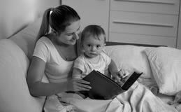 Schwarzes weißes Porträt ADN der Mutter mit dem Baby, das im Bett- und Lesebuch liegt Lizenzfreie Stockfotos