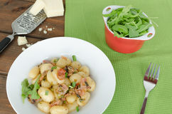 Schwarzwald gnocchi with ham, onion and wine. With arugula salad royalty free stock images