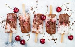 SchwarzwaldSchokoladenfondanteis am stiel mit gebratenen Kirschen und Kokosnusscreme Sahnige Wassereise des strengen Vegetariers, Stockbilder