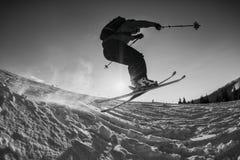Schwarzweißaufnahme des freiem Skifahrerspringens Stockfotos