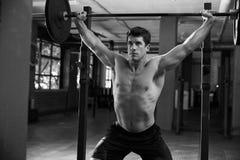 Schwarzweißaufnahme des Mannes in Turnhallen-anhebenden Gewichten Stockfotos