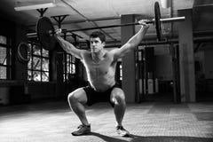 Schwarzweißaufnahme des Mannes in Turnhallen-anhebenden Gewichten Stockfoto