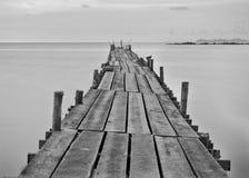 Schwarzweißfotografie eines hölzernen Piers des Strandes Lizenzfreie Stockfotos